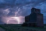 Lightning strikes behind an old grain elevator in rural Saskatchewan during a summer thunderstorm.