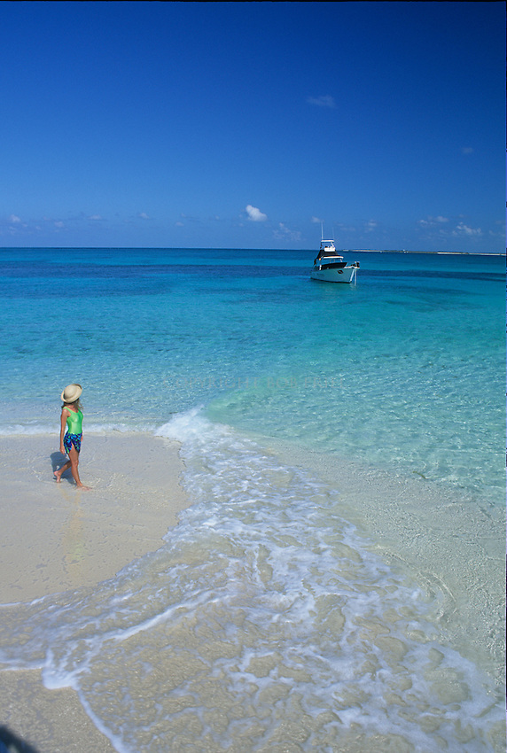 Girl and boat at beach on uninhabited island in the Abacos