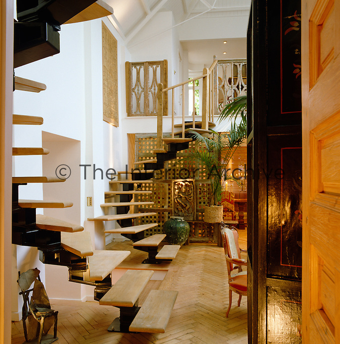 A pair of curved open staircases flank the main entrance of this ethnically furnished living space and lead up to the mezzanine floor