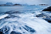 Waves wash across rocky coastline of Vestvagoy with mountain peaks rising in distance, near Stamusnd, Lofoten islands, Norway