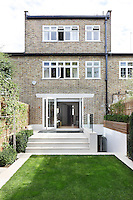 Patio doors open onto a paved area at the rear of the house with steps leading down to a neatly kept lawn