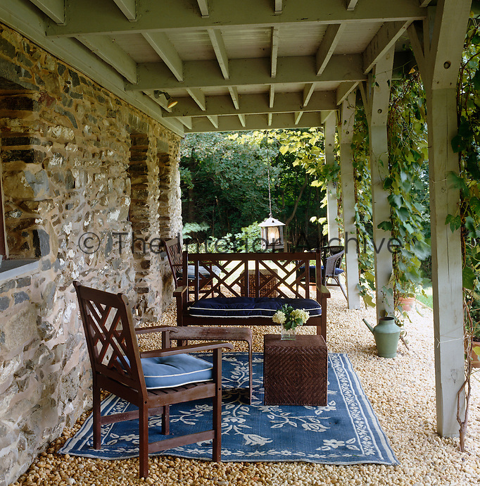 A comfortable seating area beneath this ivy covered loggia benefits from a cotton rug laid over the gravel