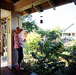 a woman drinking tea on front porch looking out over the garden