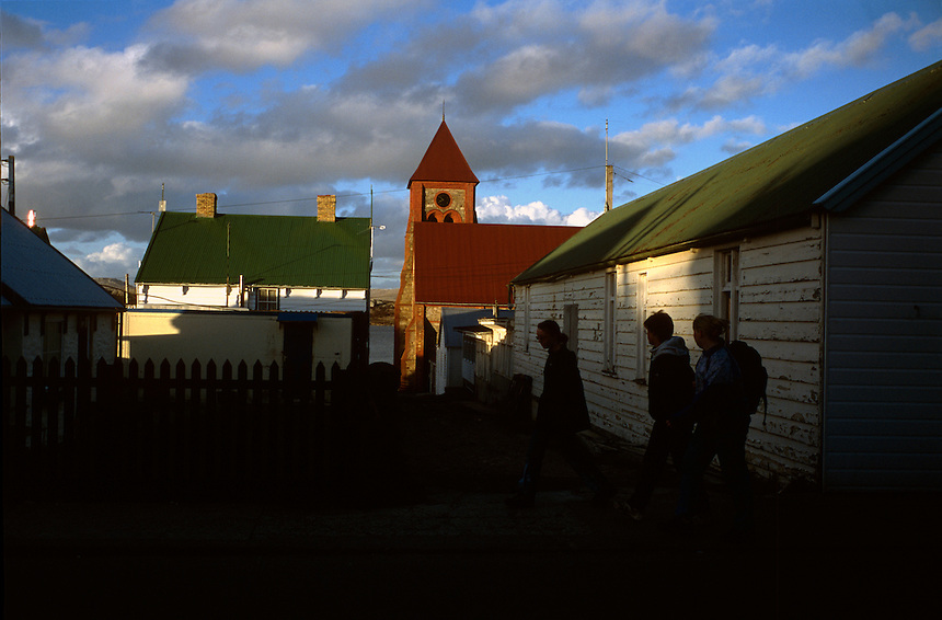 Pedestrians walk the narrow streets of Port Stanley, Falkland Islands. Great Britain repelled an invasion by Argentine troops in 1982. Now 20 years later, many Argentines are visiting the islands for the first time. They are often greeted by wary Falklanders.