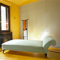 A wall of fitted cupboards and a chaise longue dominate this dressing room with floor and walls painted a buttercup yellow