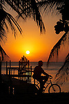 Belize, Central America - a small gate leads to a private dock on Caye Caulker where a man bicycles by looking for a sunset fishing spot.