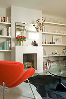 In the living room a sharp accent of orange from the Pierre Paulin armchair enlivens the grey walls and is echoed in a flower arrangement on the mantelpiece