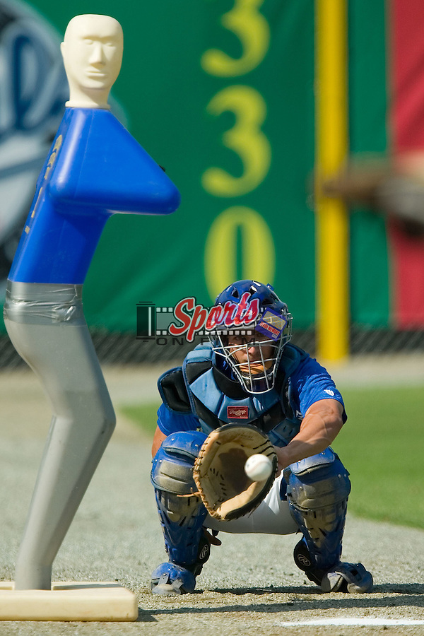 Adam Beacham (4) catches a bullpen session for Anthony Bradley (34) (not pictured) at Burlington Athletic Park in Burlington, NC, Thursday, July 12, 2007.