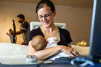 A mother doing home working at her computer while breastfeeding her baby. Her husband in the background is using his excercise machine after coming home from his job.<br /> <br /> 15/05/2012<br /> Hampshire, England, UK