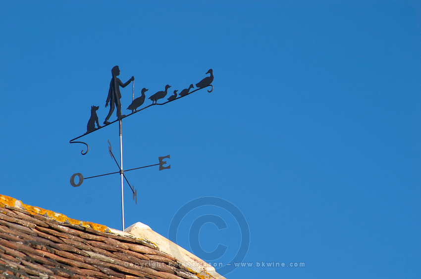 A weathercock weather vane showing a farmer with his or her geese on top of the farm house roof Ferme de Biorne duck and fowl farm Dordogne France