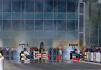 Mar 17, 2019; Gainesville, FL, USA; NHRA top fuel driver T.J. Zizzo (left) smokes the tires alongside Scott Palmer during the Gatornationals at Gainesville Raceway. Mandatory Credit: Mark J. Rebilas-USA TODAY Sports
