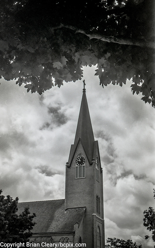 Church steeple clocktower framed by trees under cloudy skies, photo taken with 1952 vintage Kodak Signet 35, 35mm film camera on Kodak T-Max black and white film,Manitowoc, WI, July 2017.  (photo by Brian Cleary/bcpix.com)