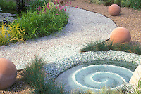"""Water"" garden of crushed  glass in spiral pattern with ornamental grasses plants, pathway, round terracotta ornaments"