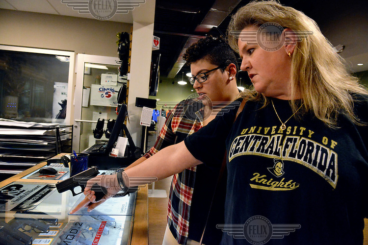 Karen McCloud (blonde), who is ex-military and works in the insurance business, with her partner Jasmine Alequin, a student and part-time security guard, trying out rental guns at Shooters World gun range and shop. The same sex couple joined the Pink Pistols (a gun advocacy group that encourages members of the LGBT community to learn to shoot and carry weapons) in the days after the Pulse nightclub massacre. They believe that the LGBT community is vulnerable to hate crimes and needs to protect itself. They are both taking concealed weapon courses and are practising their shooting skills.
