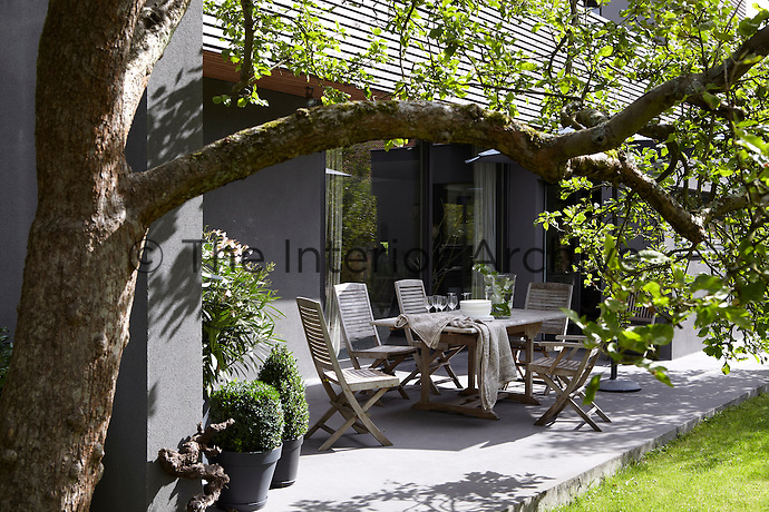 The terrace overlooking the garden is furnished with an outdoor dining table and chairs
