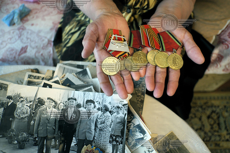 Elmira Ishmuratova shows Jubilee medals her father received (on the photo in the middle) for his service in World War II. She was 4 years old when her family was deported to Uzbekistan. Her father was in the Red Army fighting the Germans and when he returned in 1946 he was told that his family had been deported to Uzbekistan. In 1997, Ishmuratova's family wanted to return Crimea, but they were not allowed so they settled in the village of Novoalekseyevka in the Kherson region of Ukraine close to the border with Crimea.