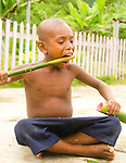 Boy eats guava mashed up in bamboo, Lobo Village.