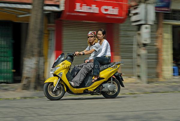 Asia, Vietnam, Hanoi. Hanoi old quarter. Cool couple on motorbike rushing through Hanoi.