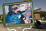 Poster, and gunship commemorating the Iran-Iraq war, Behesht-e Zahra cemetary, Tehran, Iran, 10 July 2005. P<br />