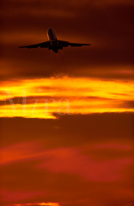 A commercial jetliner takes off into a fiery orange sky as heat waves streak the sky.