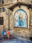 A mother and son eat ice-cream next to a frescoe of a mother and child, Mary with baby Jesus, San Gimignano, Siena-Tuscano, Italy