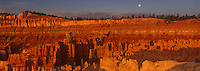 904000021 panoramic view of a full moon rises above the silent city hoodoos turned deep red and yellow by the setting sun in bryce canyon national park utah