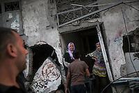 "In this Saturday, Aug. 16, 2014 photo, a Palestinian family stand at the entrance of their house after it was partially distroyed by artillery shelling during the ""Protective Edge"" Israeli military operation in Beit Hoanoun neighborhood in Gaza City. After a five days truce was declared on 13th August between Hamas and Israel, civilian population went back to what remains from their houses and goods in Gaza Strip. (Photo/Narciso Contreras)"