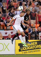 Chris Tierney (8) of the New England Revolution goes up for a header with Nick DeLeon (18) of D.C. United during a Major League Soccer game at RFK Stadium in Washington, DC.  New England defeated D.C. United, 2-1.
