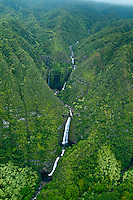An aerial view of a multi-tiered waterfall in a remote Moloka'i valley.