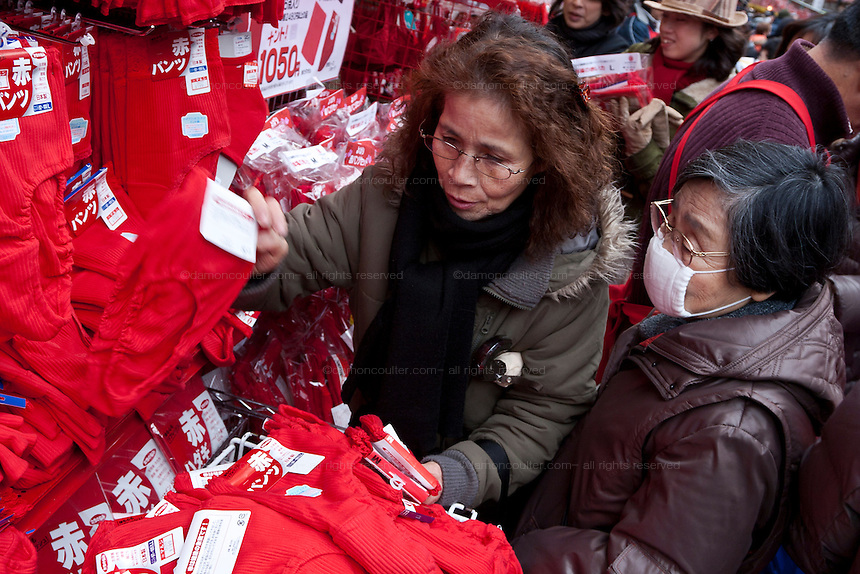 Japanese women sort through the iconic red underwear that is supposed to bring health to the wearer. Sugamo, Tokyo, Japan. Saturday January 24th 2009. Sugamo is affectionately known as the old lady Harajuku, in reference to the Mecca for youth fashions in the South of Tokyo, and is a popular place for Tokyo's increasingly aged population. The red underwear on sale here has become an iconic garment to Sugamo,