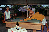 Cajari, Amapa, Brazil. Caboclos playing pool in a bar with a large satellite dish beyond and two bottles of beer.