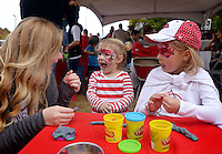 NWA Democrat-Gazette/BEN GOFF @NWABENGOFF<br /> Anna Castleberry (from left), an Arkansas student from Fayetteville, helps Caroline Murphy, 2, and sister Claire Murphy, 6, of Fayetteville make animals out of Play-Doh on Saturday Oct. 24, 2014 while tailgating outside Razorback Stadium in Fayetteville before the football game against Auburn.