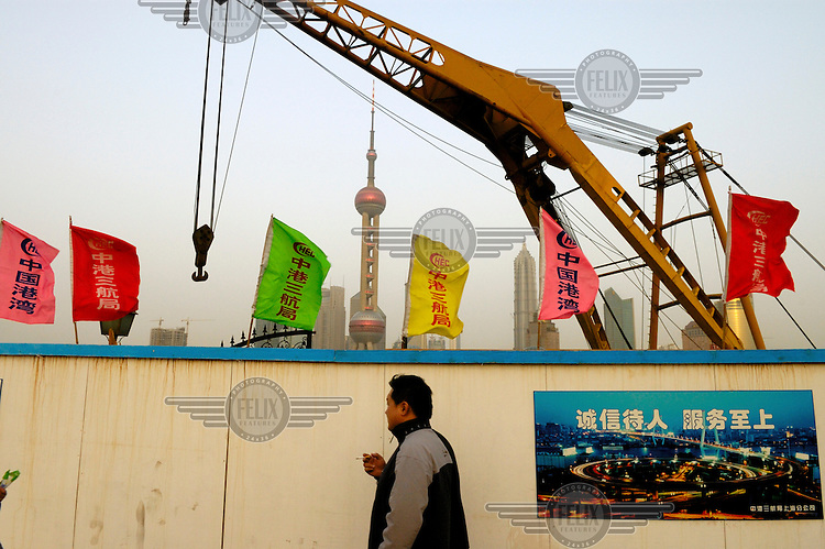 A crane and Pudong skyscrapers, including the Oriental Pearl TV Tower, rising behind a temporary wall hiding a construction site.