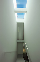 The staircase is flooded with natural light from a large skylight positioned directly above it