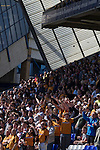 Visiting Wolves supporters in the Gil Merrick stand at St. Andrew's stadium, cheering as their team takes the field prior to Birmingham City's Barclay's Premier League match with Wolverhampton Wanderers. Both clubs were battling against relegation from  England's top division. The match ended in a 1-1 draw, watched by a crowd of 26,027.