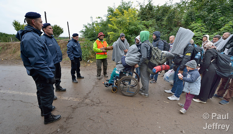 Refugees and migrants on their way to western Europe stop at the border into Croatia near the Serbian village of Berkasovo. As Croatian police keep watch, a Czech volunteer (in the orange vest) explains their legal rights and what awaits them in Croatia.