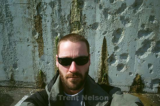 Trent Nelson with shot-up wall.<br />
