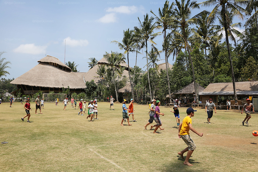 Boys and girls students playing football during break with 'Heart of School in background'<br /><br />The Green School (Bali) is one of a kind in Indonesia. It is a private, kindergarten to secondary International school located along the Ayung River near Ubud, Bali, Indonesia. The school buildings are of ecologically-sustainable design made primarily of bamboo, also using local grass and mud walls. There are over 600 students coming from over 40 countries with a percentage of scholarships for local Indonesian students.<br /><br />The impressive three-domed &quot;Heart of School Building&quot; is 60 metres long and uses 2500 bamboo poles. The school also utilizes renewable building materials for some of its other needs, and almost everything, even the desks, chairs, some of the clothes and football goal posts are made of bamboo.<br /><br />The educational focus is on ecological sustainability. Subjects taught include English, mathematics and science, including ecology, the environment and sustainability, as well as the creative arts, global perspectives and environmental management. This educational establishment is unlike other international schools in Indonesia. <br /><br />Renewable energy sources, including solar power and hydroelectric vortex, provide over 50% of the energy needs of the school. The school has an organic permaculture system and prepares students to become stewards of the environment. <br /><br />The school was founded by John and Cynthia Hardy in 2008.