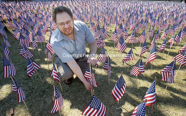 SEYMOUR, CT. 02 April 2009-040209SV09--Rev. Greg Dawson of the Seymour Congregational Church sets a flag in the Field of Flags Memorial, which is a traveling memorial that honors those service men and women who died in Iraq and Afghanistan. There are 4929 flags in the memorial sitting outside the church in Seymour and two will be added Sunday for two more soldiers that died in Afghanistan. Steven Valenti Republican-American