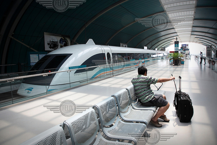 A passenger waits on the platform at Longyang Road Station next to a Maglev Train. The train runs to and from Pudong International Airport. The train runs at a top operational speed of 431 km/h (268 mph), making the journey of 30 km (18.6 mi) in 7 minutes and 20 seconds.