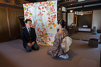 Japan, Okayama Prefecture, Kurashiki. Hasimaya House and Kimono Shop. Fifth generation owner showing intricately woven kimono to customer. MR