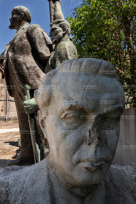 Albania. Tirana. Back yard of the National Gallery of Arts. Old Socialist Realism Statues from the Communist Era. A statue with a broken nose from Enver Halil Hoxha (16 October 1908 – 11 April 1985) who was an Albanian communist politician who served as the head of state of Albania from 1944 until his death in 1985, as the First Secretary of the Party of Labour of Albania. He was chairman of the Democratic Front of Albania and commander-in-chief of the armed forces from 1944 until his death. A bronze statue of a man holding a rifle in his left hand and raising his right arm to the sky. A bronze giant statue of Vladimir Ilyich Ulyanov, better known by the alias Lenin (22 April 1870 – 21 January 1924), who was a Russian communist revolutionary, politician and political theorist. He served as head of government of Soviet Russia from 1917 to 1924 and of the Soviet Union from 1922 to 1924. Under his administration, Russia and then the wider Soviet Union became a one-party communist state governed by the Russian Communist Party. Ideologically a Marxist, he developed political theories known as Leninism. Tirana is the capital and most populous city of the Republic of Albania. The city is also the capital of the surrounding county of Tirana, one of 12 constituent counties of the country. 27.5.2018 © 2018 Didier Ruef