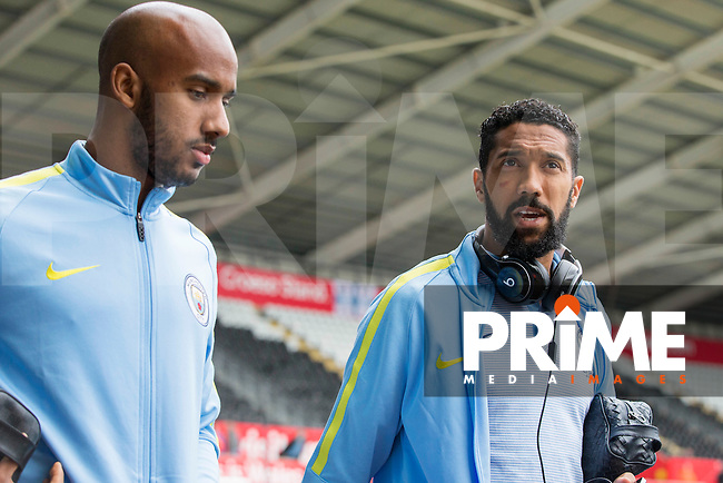 Gael Clichy of Manchester City speaks with team-mate Fabian Delph as they arrive for the EPL - Premier League match between Swansea City and Manchester City at the Liberty Stadium, Swansea, Wales on 24 September 2016. Photo by Mark  Hawkins.