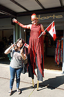 VANCOUVER, CANADA, 1st July 2013. Young woman of Asian descent standing next to a woman on stilts at Canada Day celebrations on Granville Island in Vancouver, BC. Canada Day or Fete du Canada is an annual national holiday celebrating Canada's birth as a nation  in 1867.