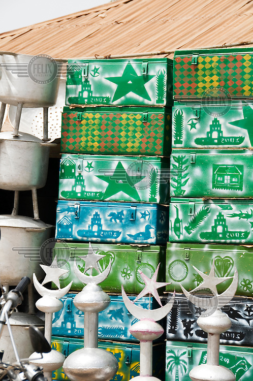 Street market stall selling metal trunks for migrant workers.
