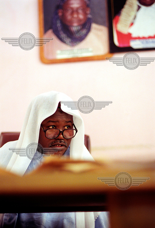 photo: Sven Torfinn.Nigeria, Kano, Kano State, october 2002.Sharia court, judge, above him on the wall two portraits of his predecessor. Sharia law was working on a community / local level and has been practised.already hundreds of years in Northern Nigeria, but in recent years declared official jurisdiction in several northern states of Nigeria. But sentences /.verdicts by the national sharia courts such as stoning to death and amputations / choping of hands because of theft are getting now a lot of media attentions and critisism from different western organizations and goverments.