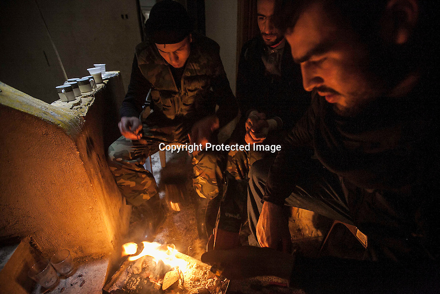 In this Friday, Dec. 07, 2012 photo, Syrian rebels make fire to keep them warm at the front line after clashes with troops loyal to Syrian President Bashar al-Assad in Aleppo, Syria. (AP Photo/Narciso Contreras)
