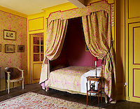 In another guest room, the walls and bed are covered in a Thevenon toile de Jouy, and the bed's alcove is lined in taffeta