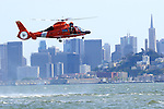 With the dummy victim positioned in the door a United States Coast Guard HH-65C Dolphin helicopter hovers above the San Francisco Bay. The helicopter and crew, based at U.S. Coast Guard Air Station San Francisco, was on a practice mission with the Coast Guard Auxilary to maintain search and rescue proficiency. Photographed 04/08