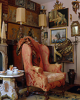 A fine 18th century armchair is covered in silk damask and sits in the corner of a living room filled with antique objects
